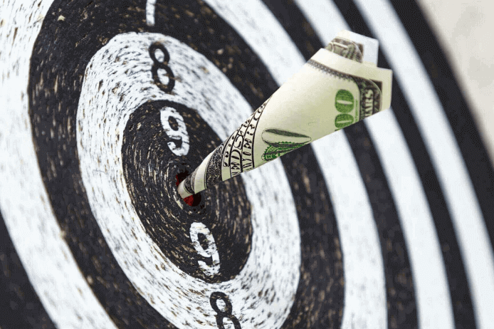 A bullseye target with money being used as the dart to portray how retailers can increase profits with accurate seasonal demand forecasting.